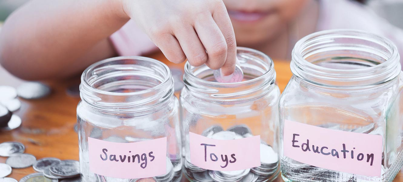 Child putting change into savings jars.