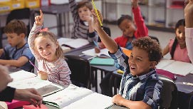 Young children in class smiling and raising their hands.